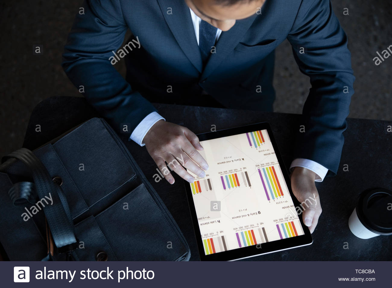 View from above businessman looking at data on digital tablet - Stock Image