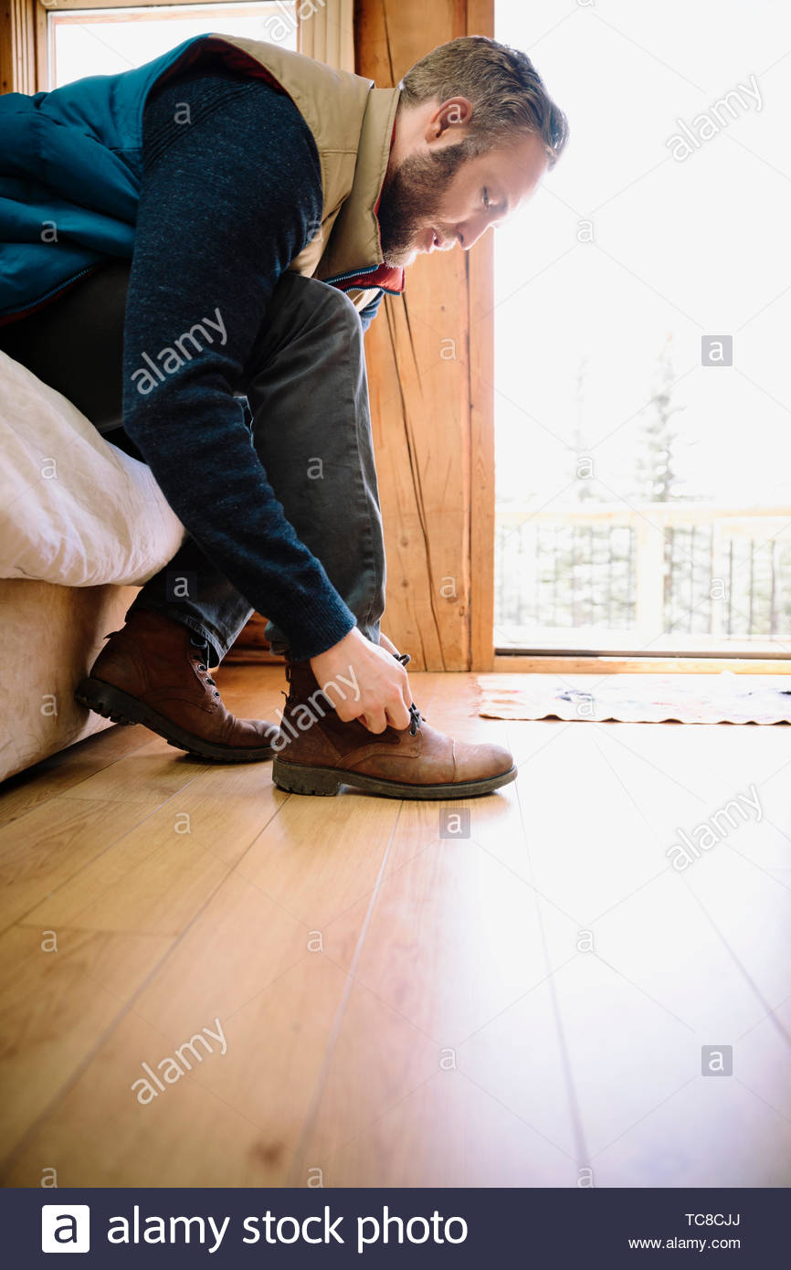 Man tying shoe at edge of bed - Stock Image