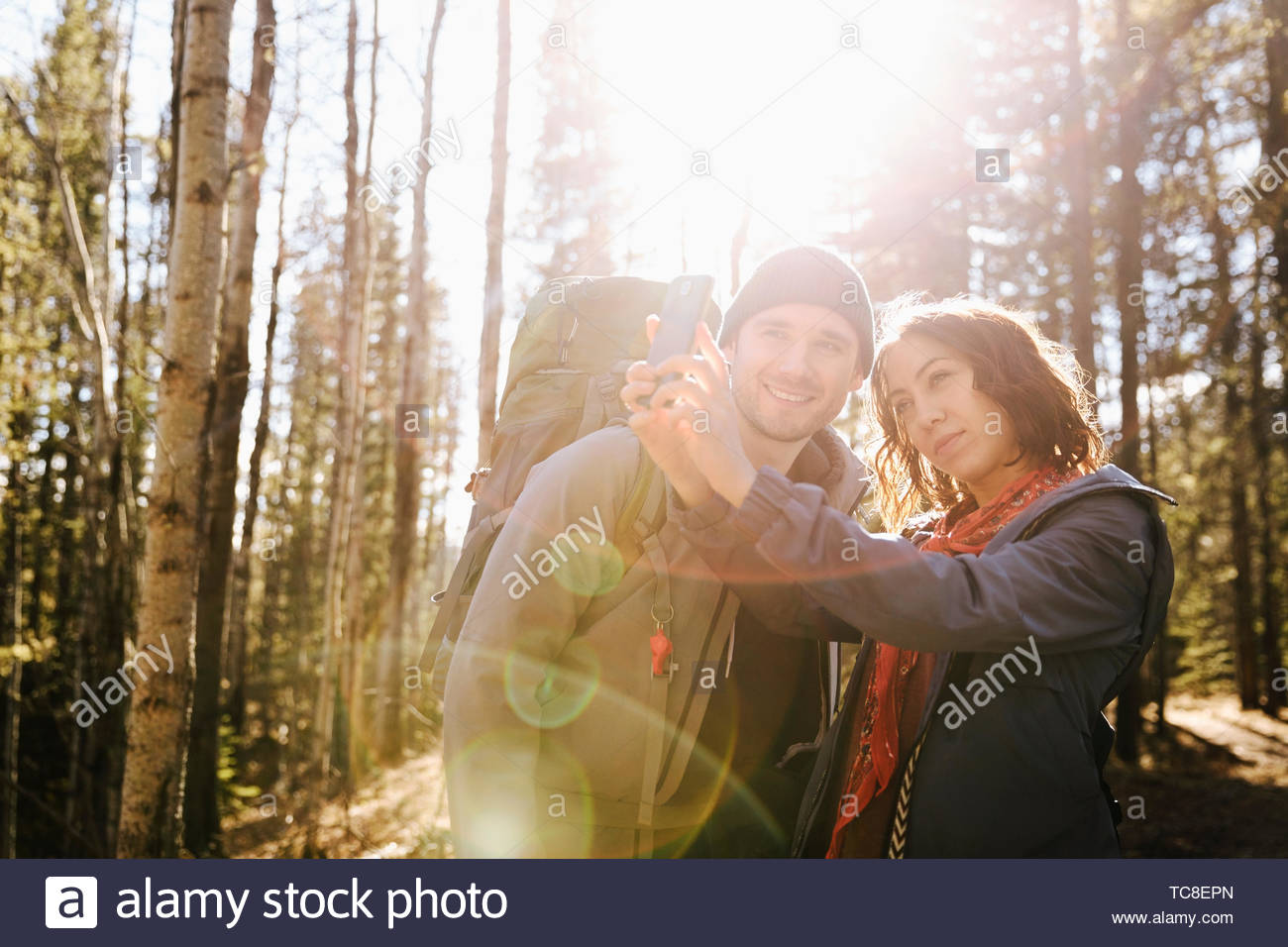 Couple taking selfie, hiking in sunny woods - Stock Image