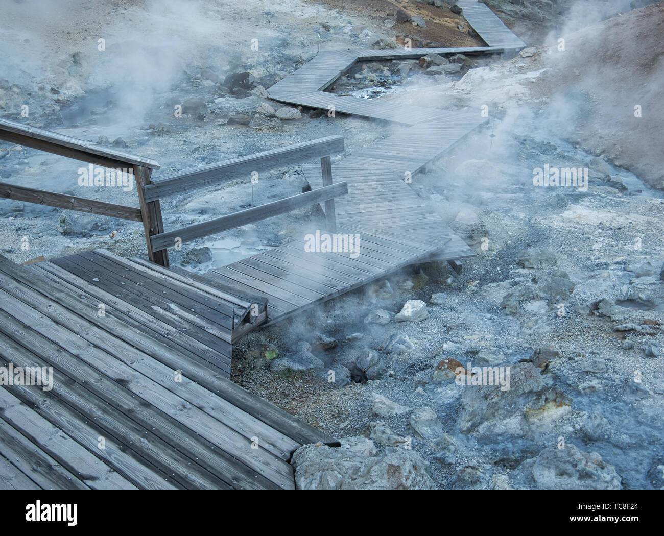 Wooden path across the steaming mud holes at Seltun is Island - Stock Image