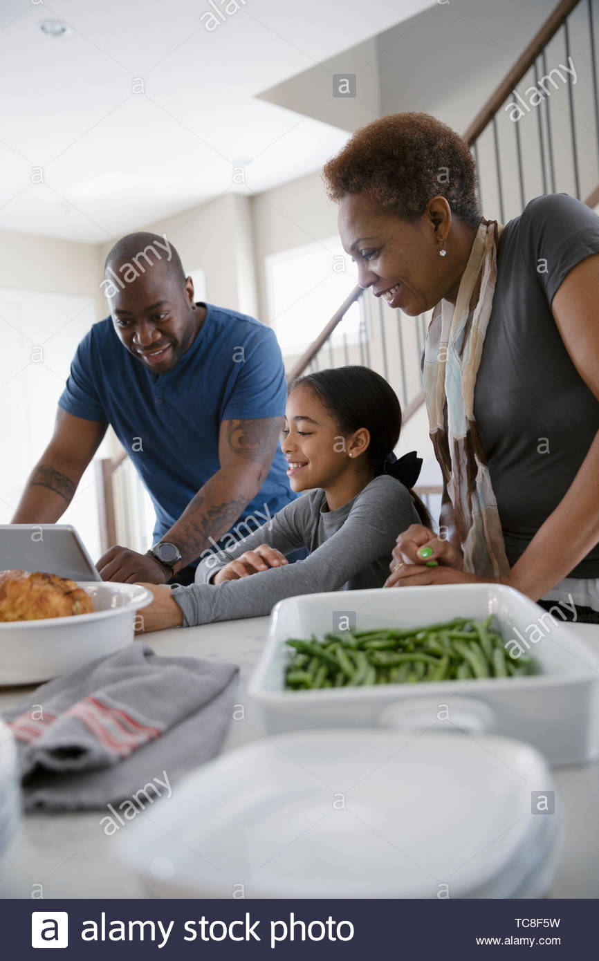 Multi-generation family with digital tablet preparing dinner in kitchen - Stock Image
