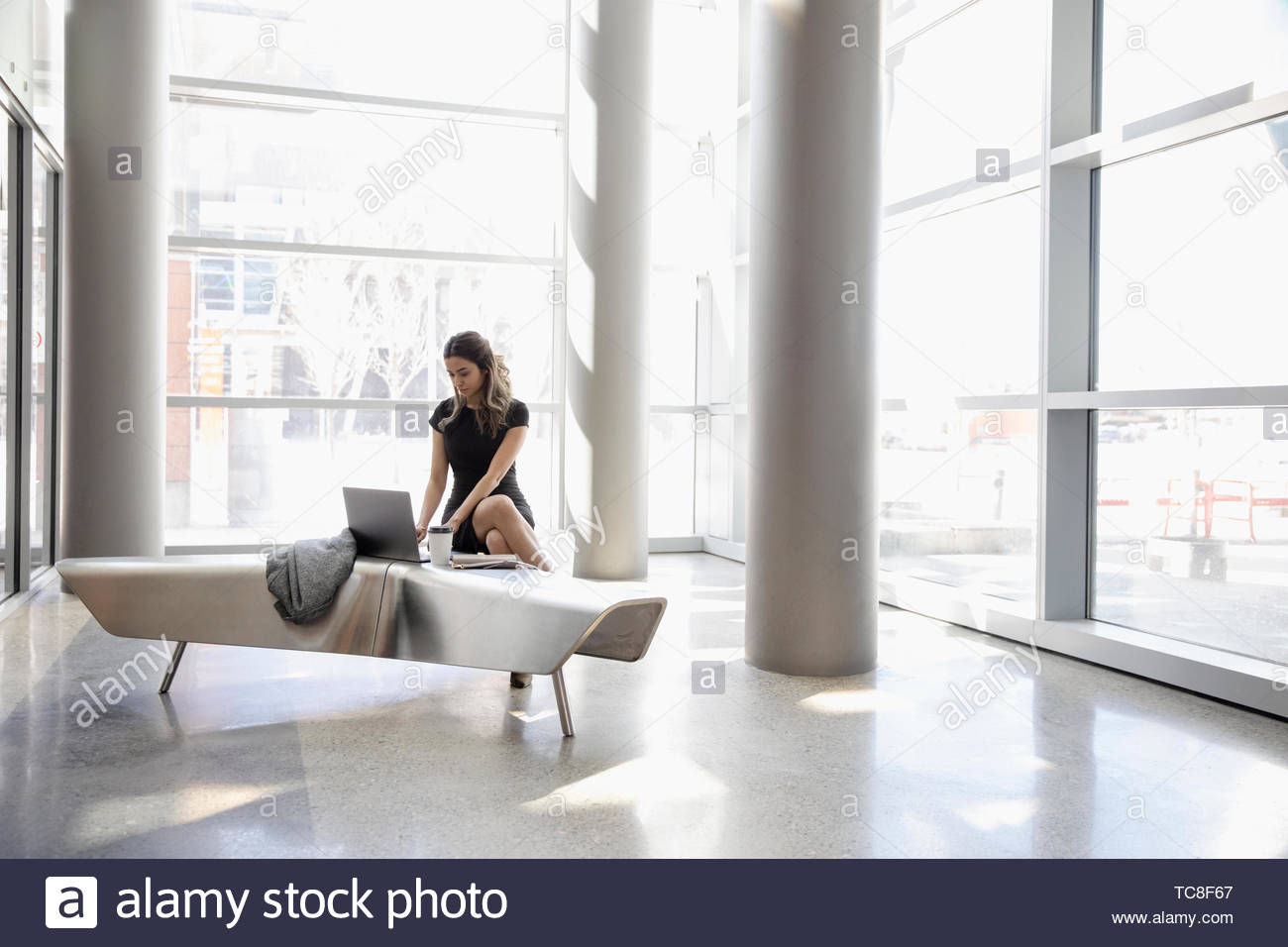 Businesswoman working at laptop in office lobby - Stock Image