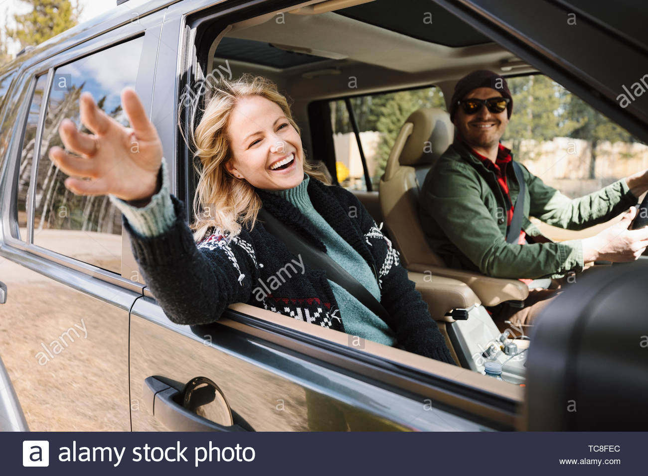 Carefree woman enjoying road trip in SUV - Stock Image