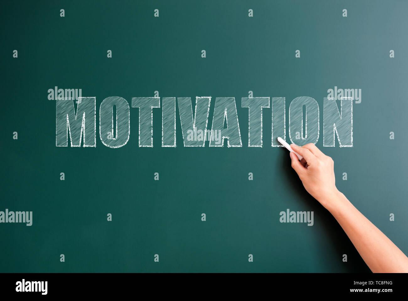 motivation written on blackboard - Stock Image