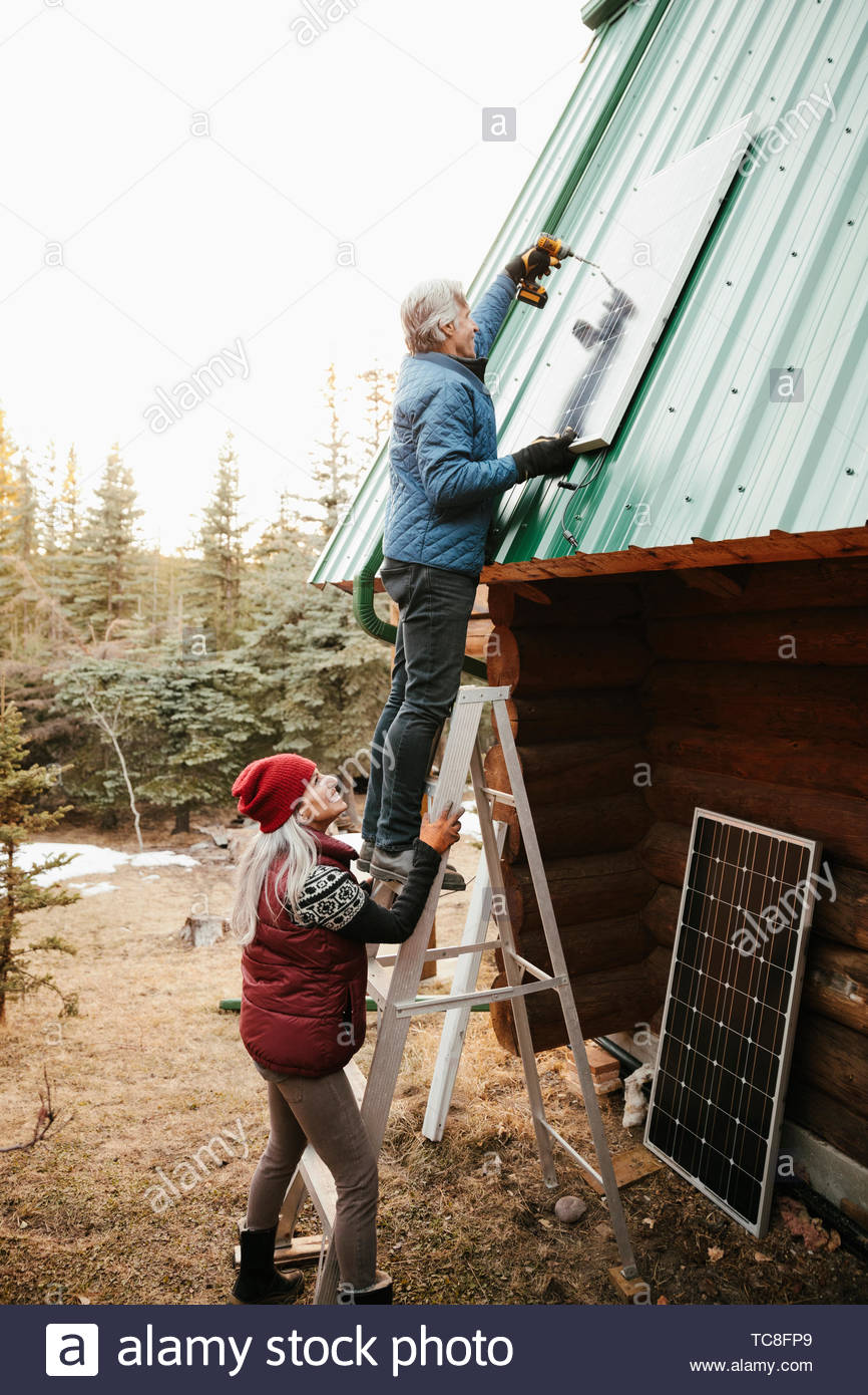 Couple installing solar panels on cabin roof - Stock Image