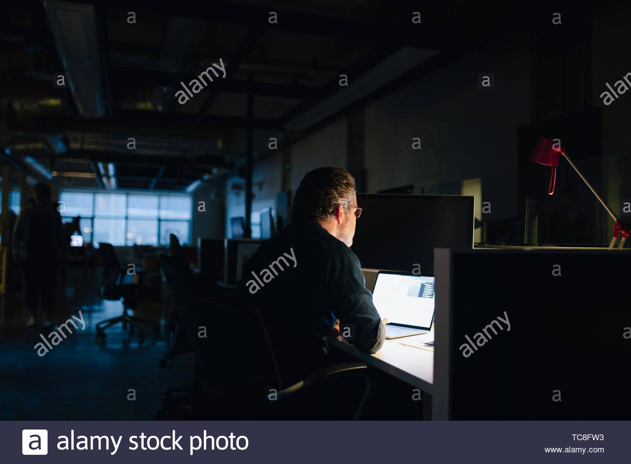 Businessman working late at laptop in dark office - Stock Image
