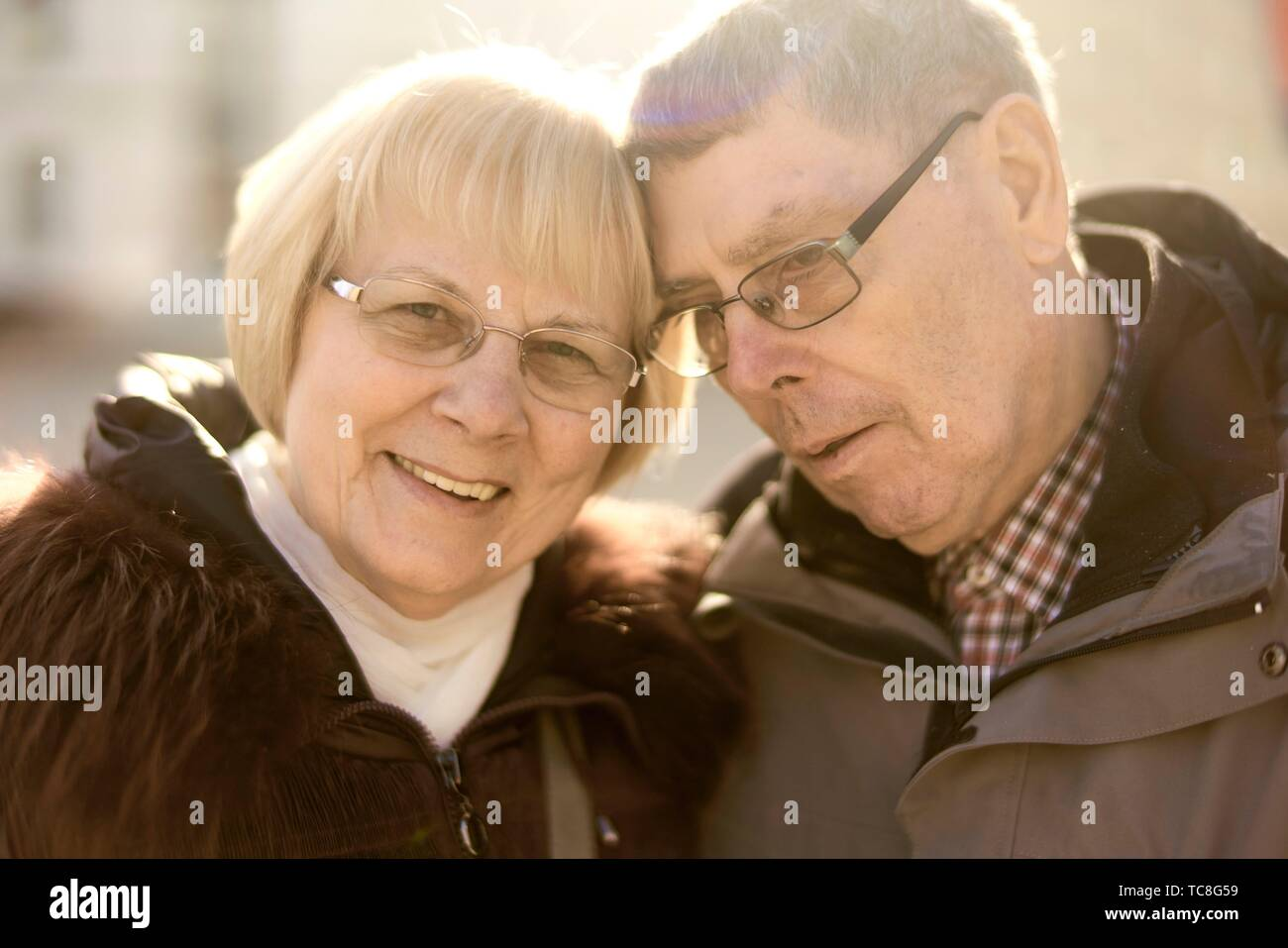 senior couple leaning heads together in sunlight, in Cottbus, Brandenburg, Germany. - Stock Image