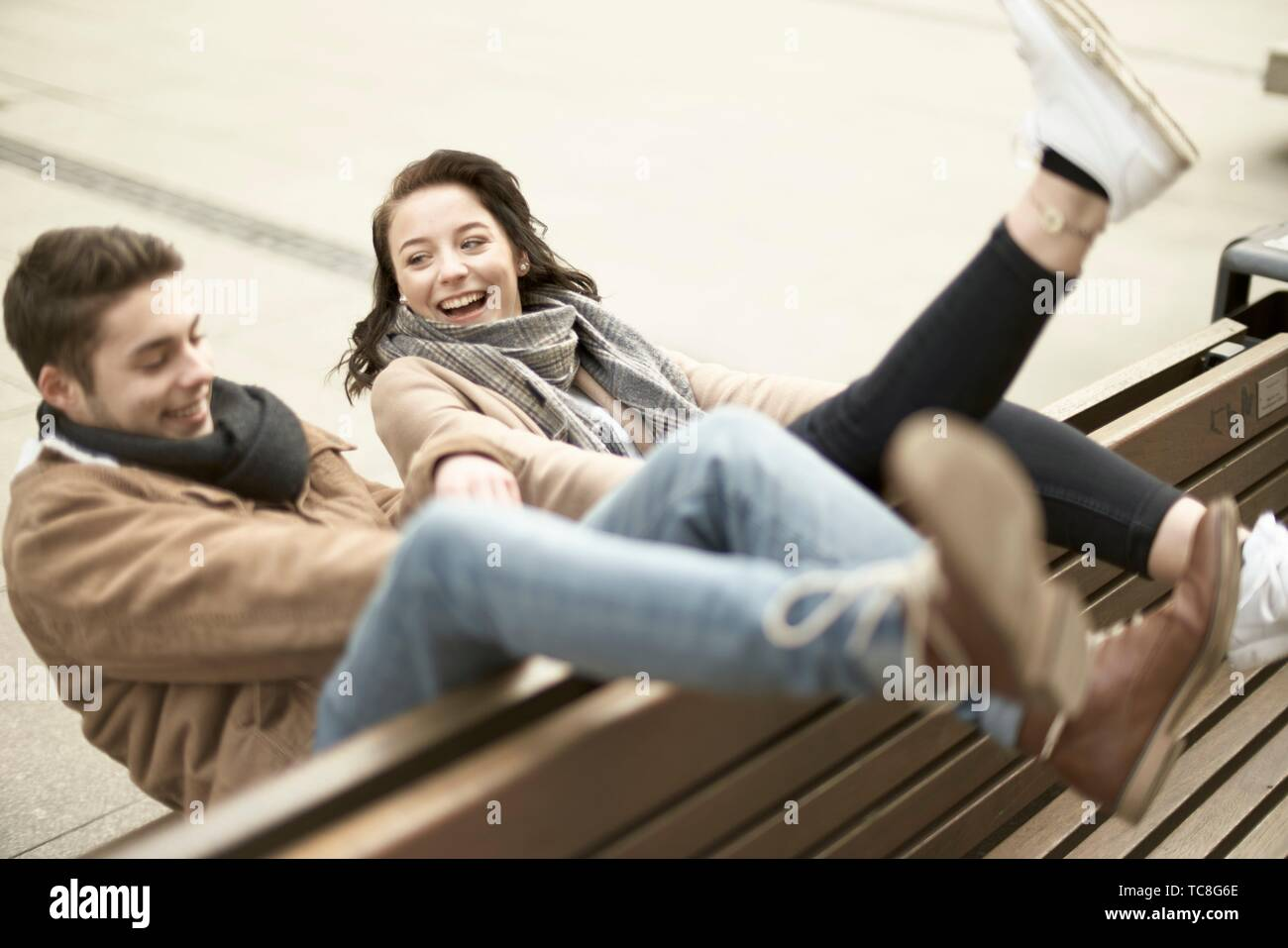 young lively teenage couple sitting on bench the wrong way round in city, hanging out together, legs up, upside down, in Cottbus, Brandenburg, Germany Stock Photo