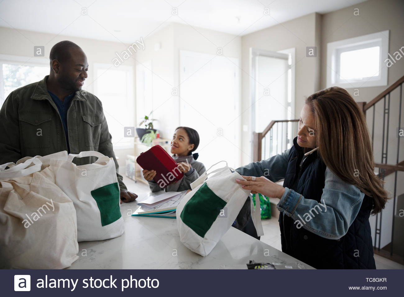 Family unloading groceries in kitchen - Stock Image