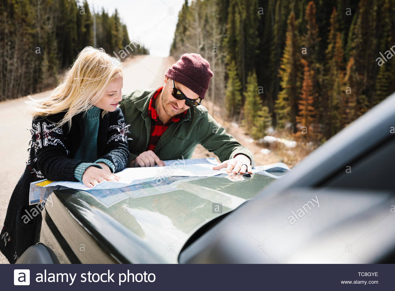 Couple looking at map on hood of car at sunny roadside Stock Photo
