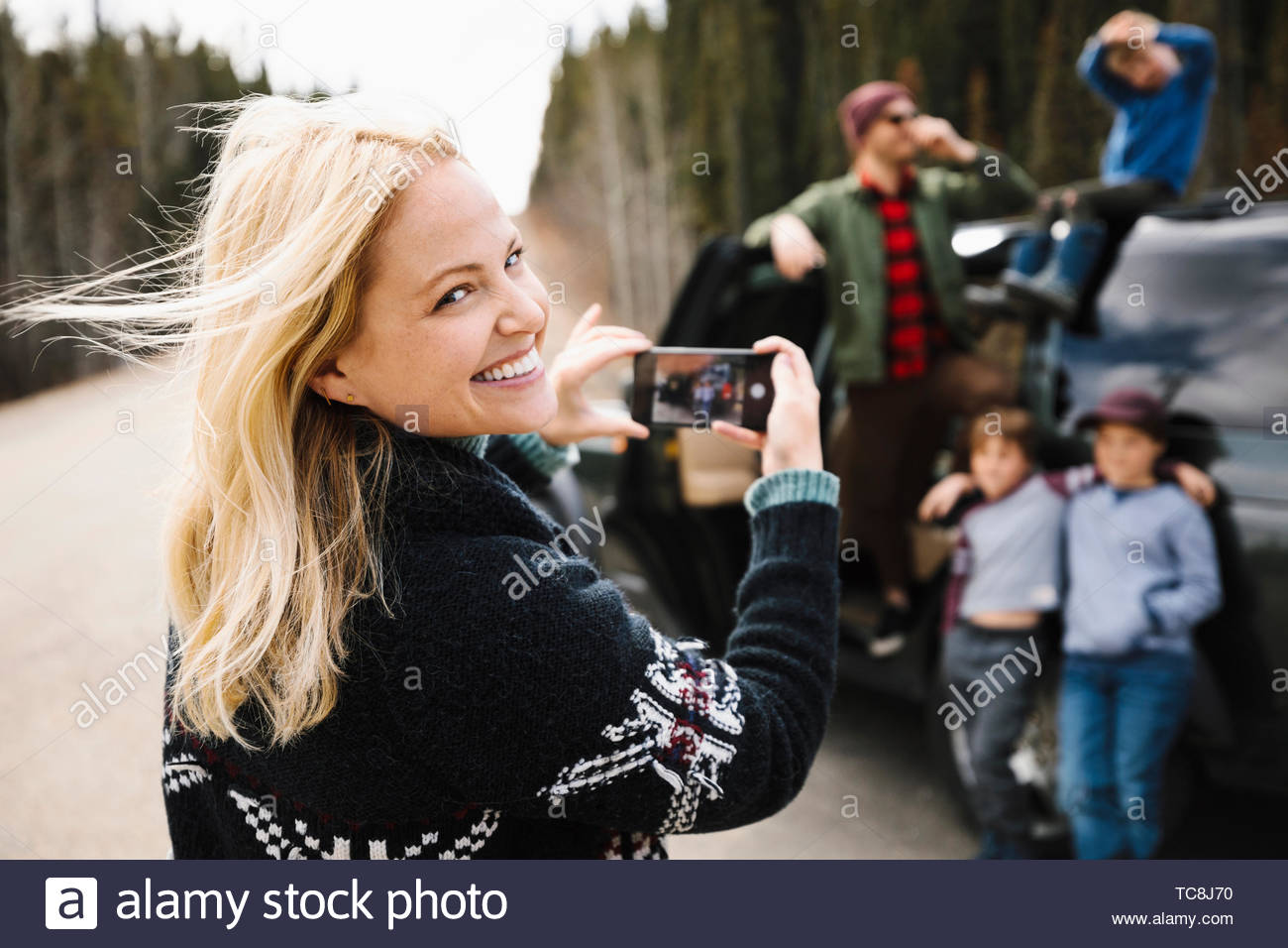 Portrait happy mother with camera phone photographing family at roadside - Stock Image