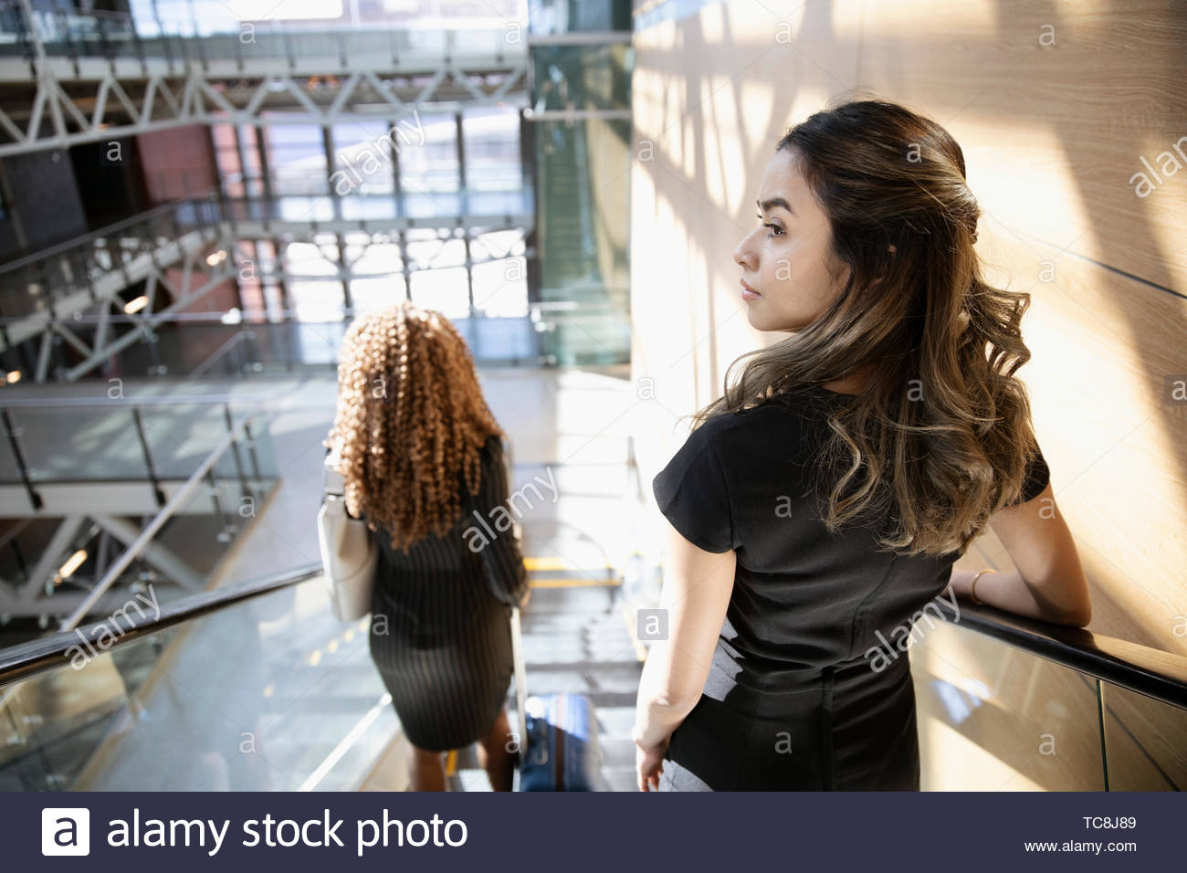 Businesswomen descending escalator in office - Stock Image