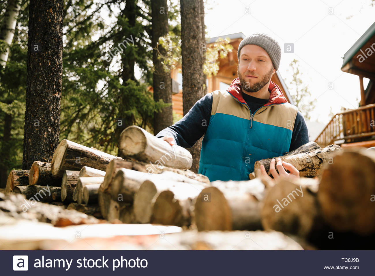 Man stacking firewood outside cabin - Stock Image