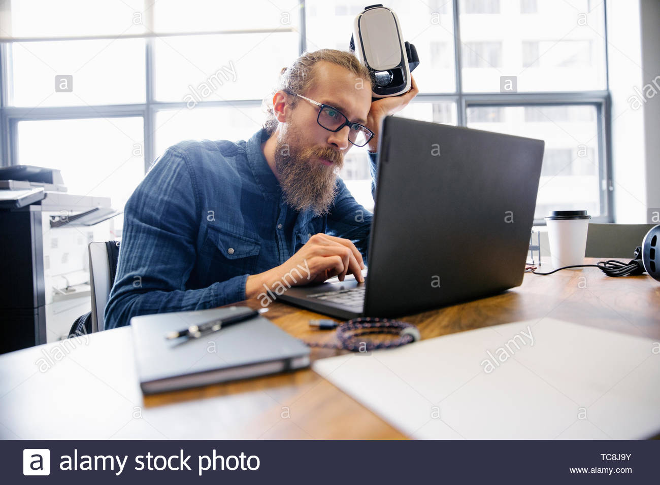 Focused computer programmer with virtual reality simulator glasses working at laptop in office - Stock Image