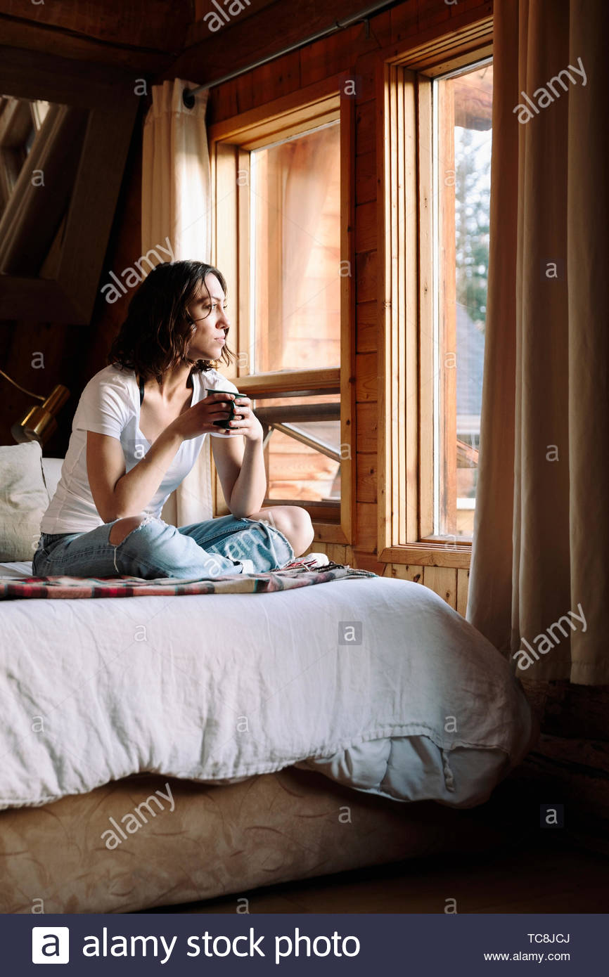 Serene woman drinking coffee on cabin bed - Stock Image