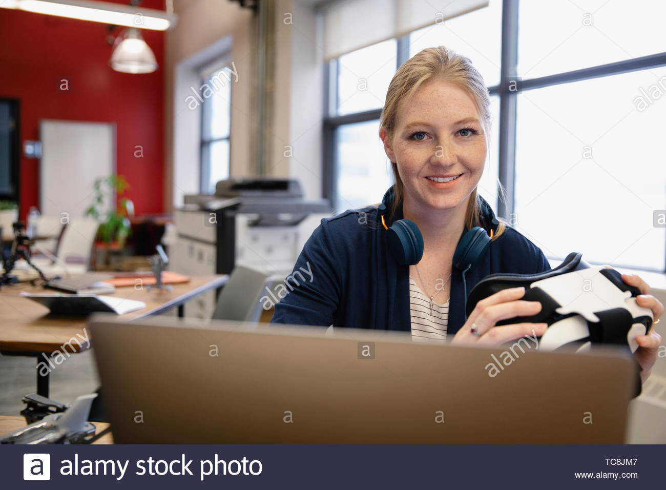 Portrait confident computer programmer with virtual reality simulator glasses working at laptop in office - Stock Image