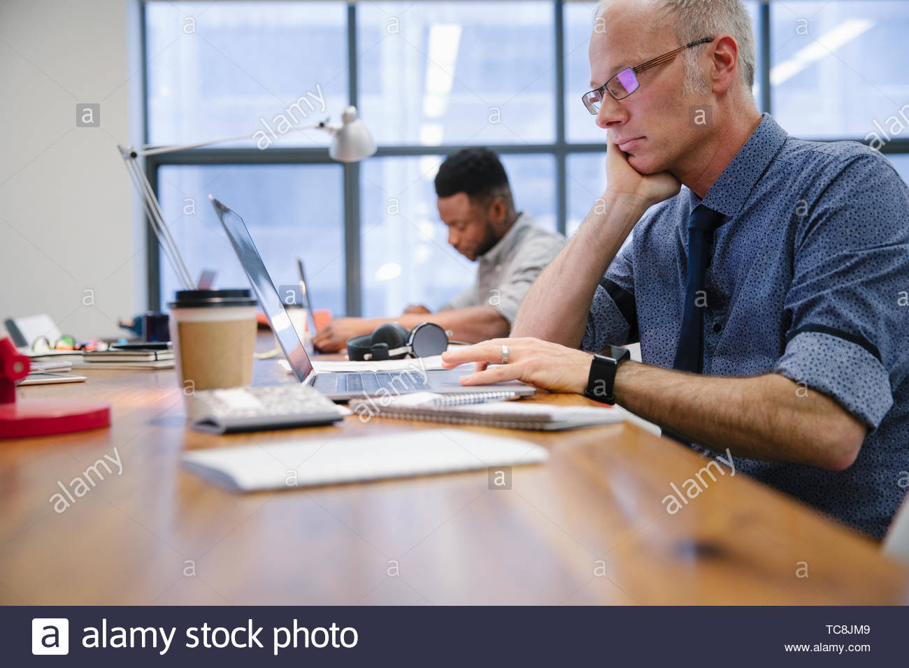Focused businessman working at laptop in coworking space Stock Photo