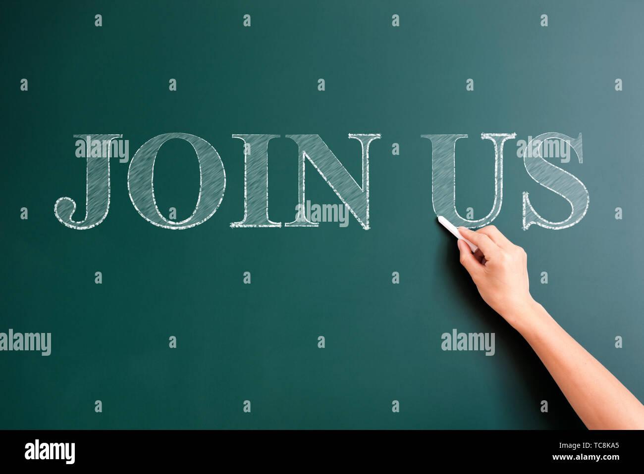 join us written on blackboard - Stock Image
