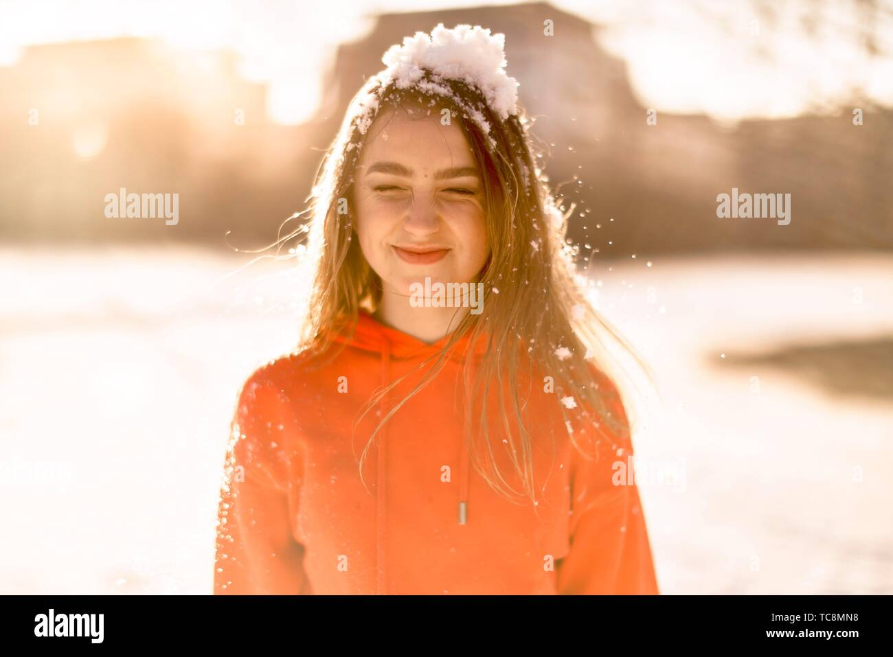 young woman with cold snow on head, squeezing eyes, winter season, wearing orange sweater, in Cottbus, Brandenburg, Germany Stock Photo
