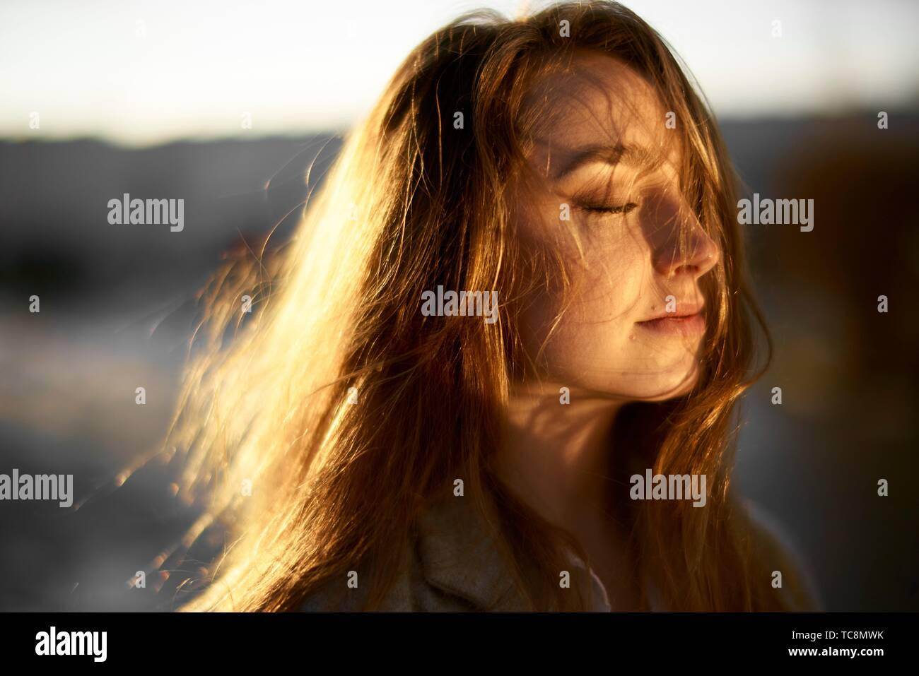 young emotive woman outdoors in warm sunlight, closed eyes, hair blowing in wind, joy, in Cottbus, Brandenburg, Germany - Stock Image