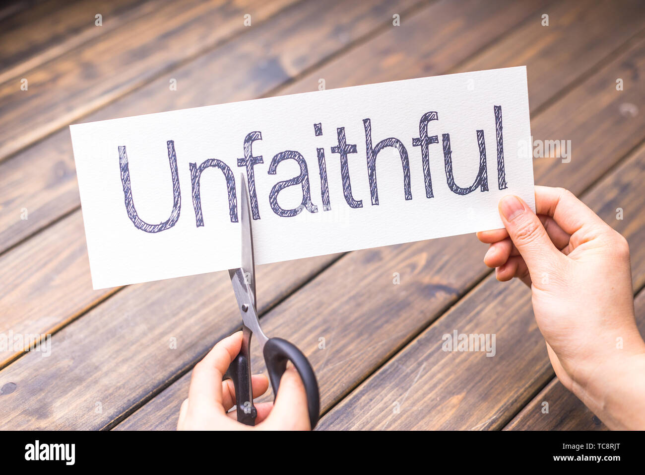 woman cuts white paper with word unfaithful on table - Stock Image