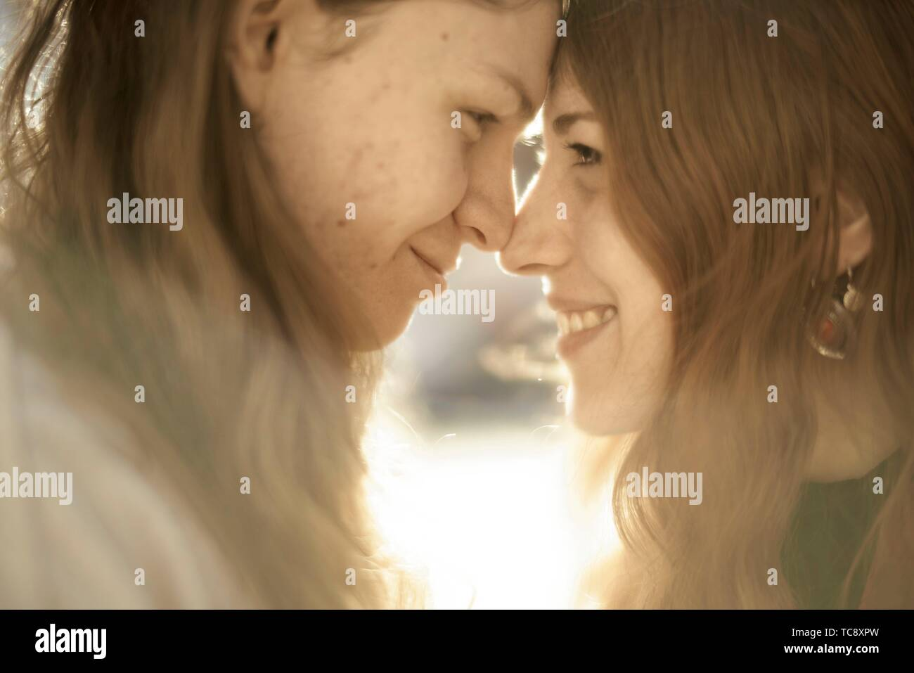 affectionate couple outdoors in sunlight, looking at each other, face to face, in Berlin, Germany - Stock Image