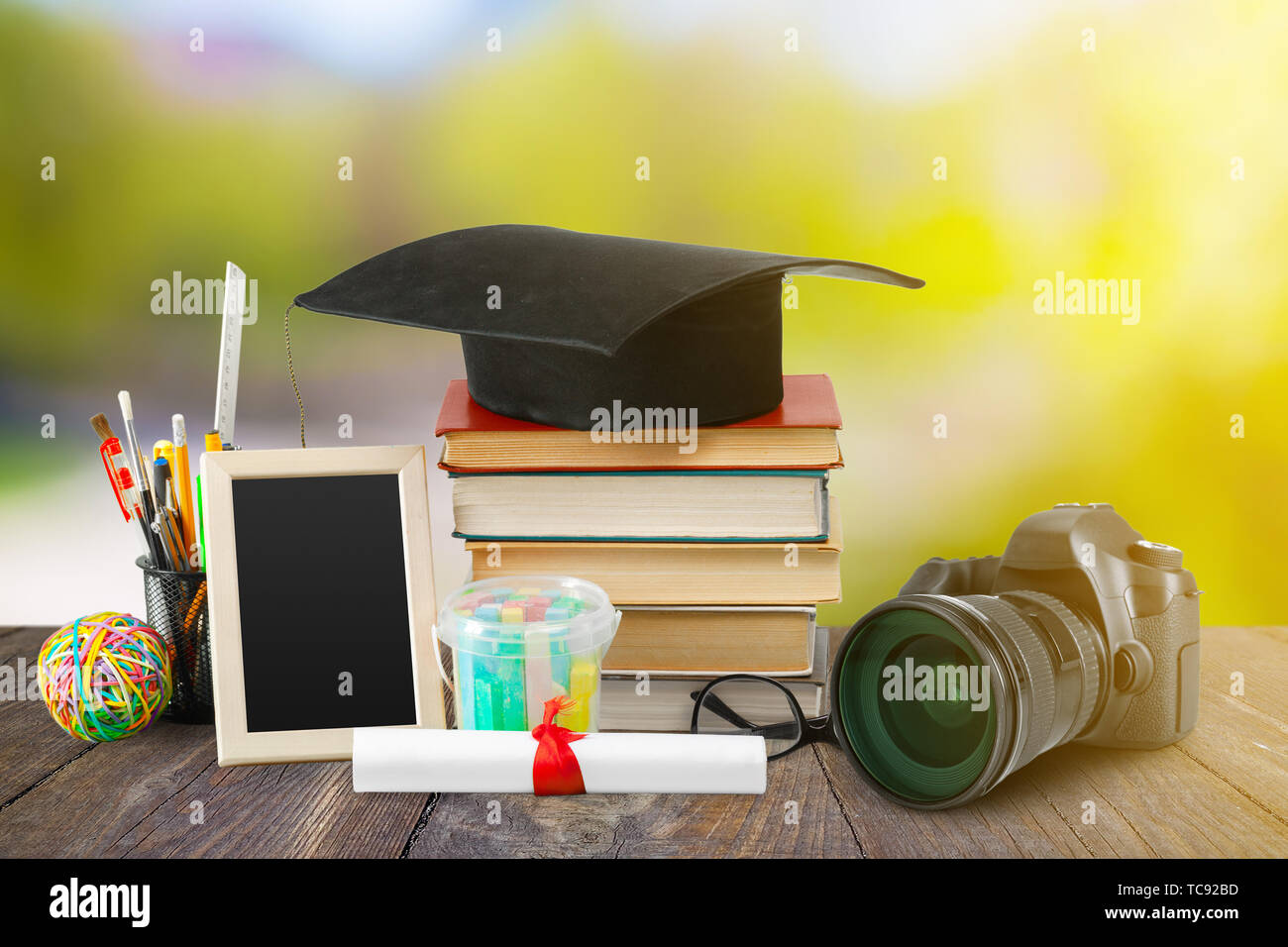 Graduation from school/university composition. Pile of books, diploma, graduation cap and camera on a desk - Stock Image