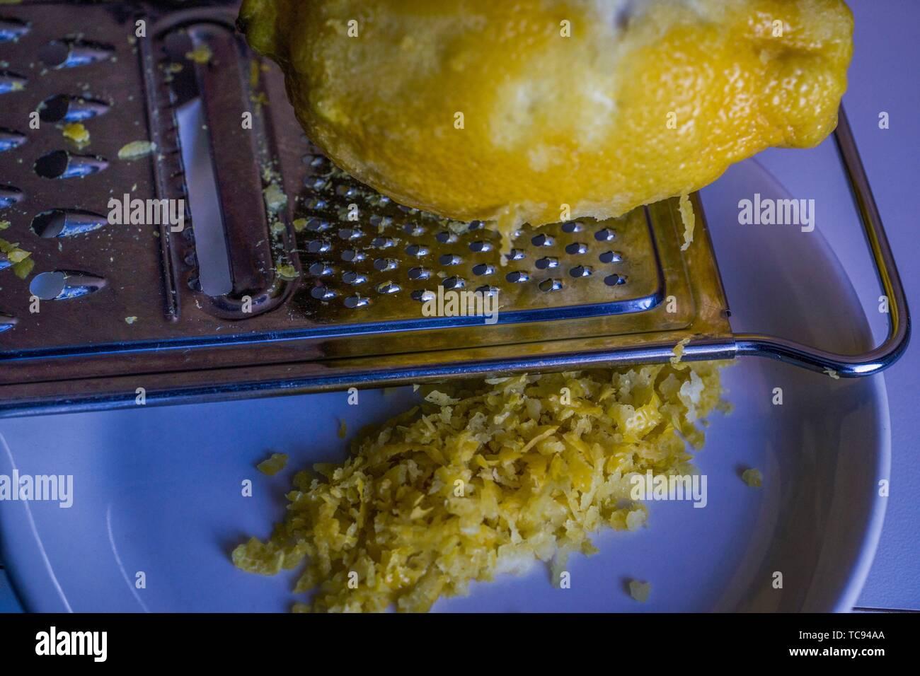 Lemon rind (zest) being grated. Macro image. - Stock Image