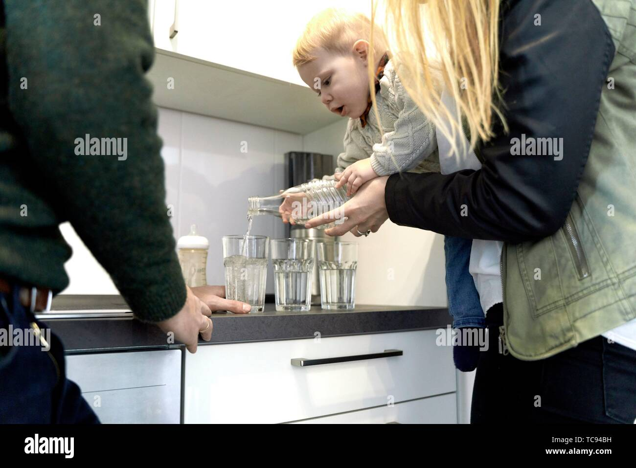 parents guiding baby toddler child filling water in drinking glasses in kitchen at home, pouring, in Cottbus, Brandenburg, Germany. - Stock Image
