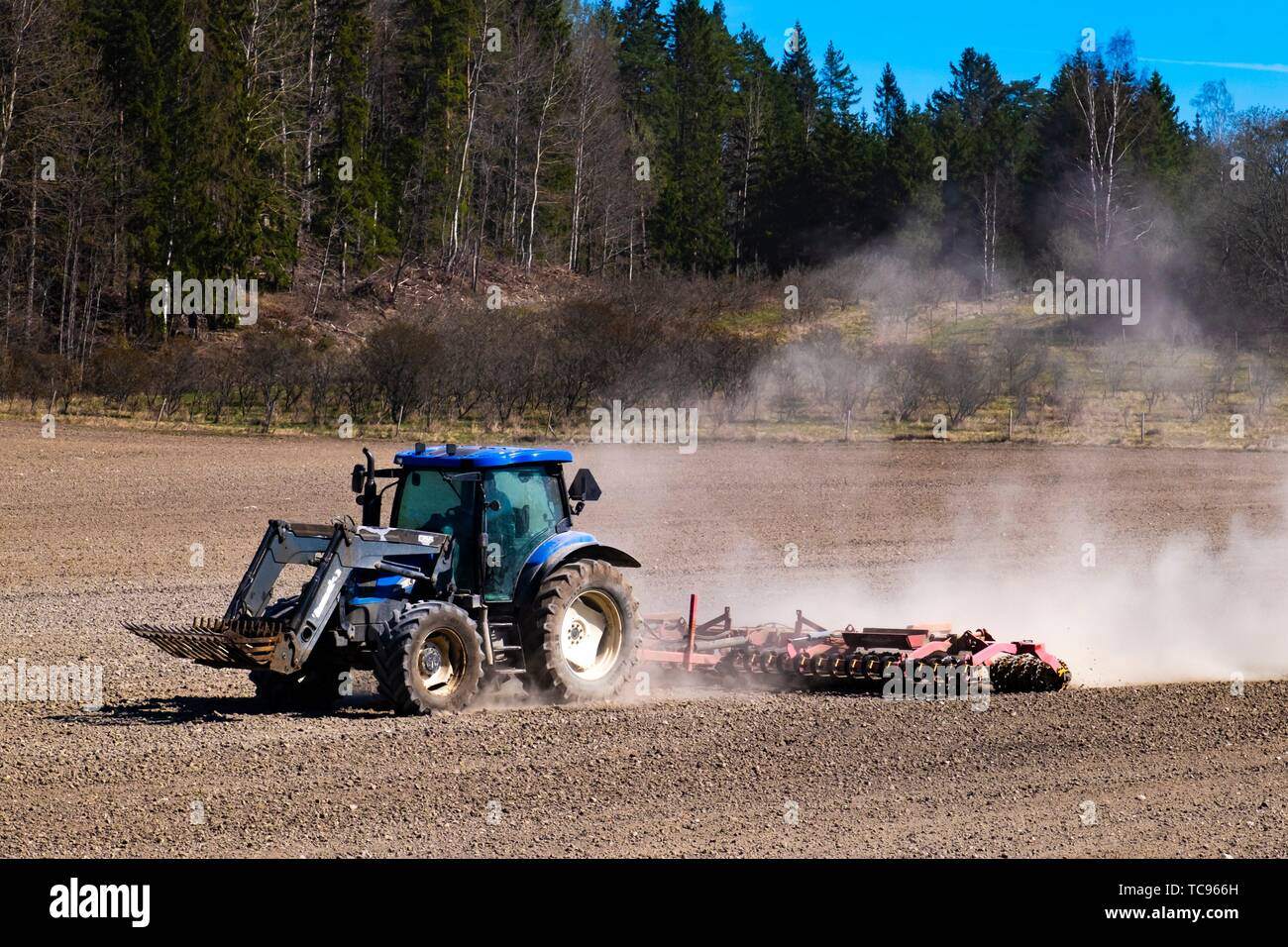 Tractor on field in Sweden. - Stock Image