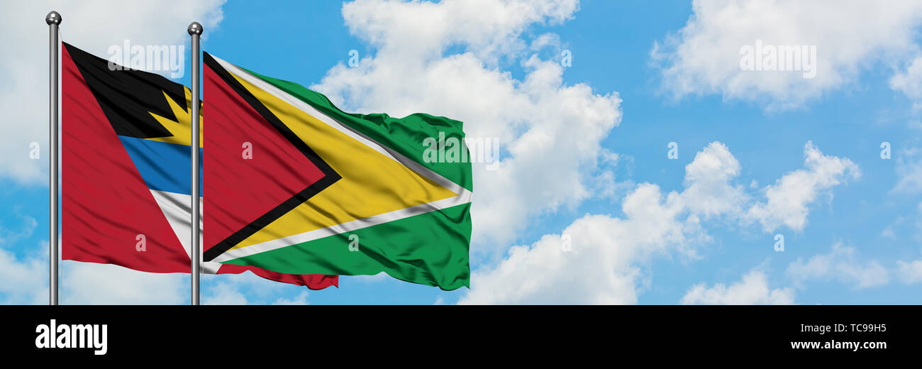 Antigua and Barbuda with Guyana flag waving in the wind against white cloudy blue sky together. Diplomacy concept, international relations. - Stock Image