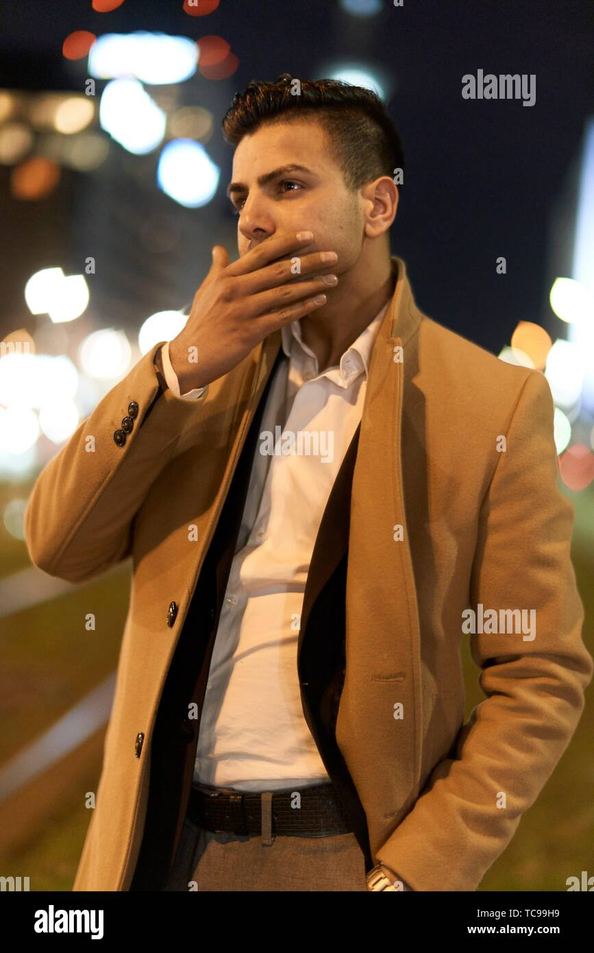 young pondering Afghan man at night, in city Berlin, Germany - Stock Image