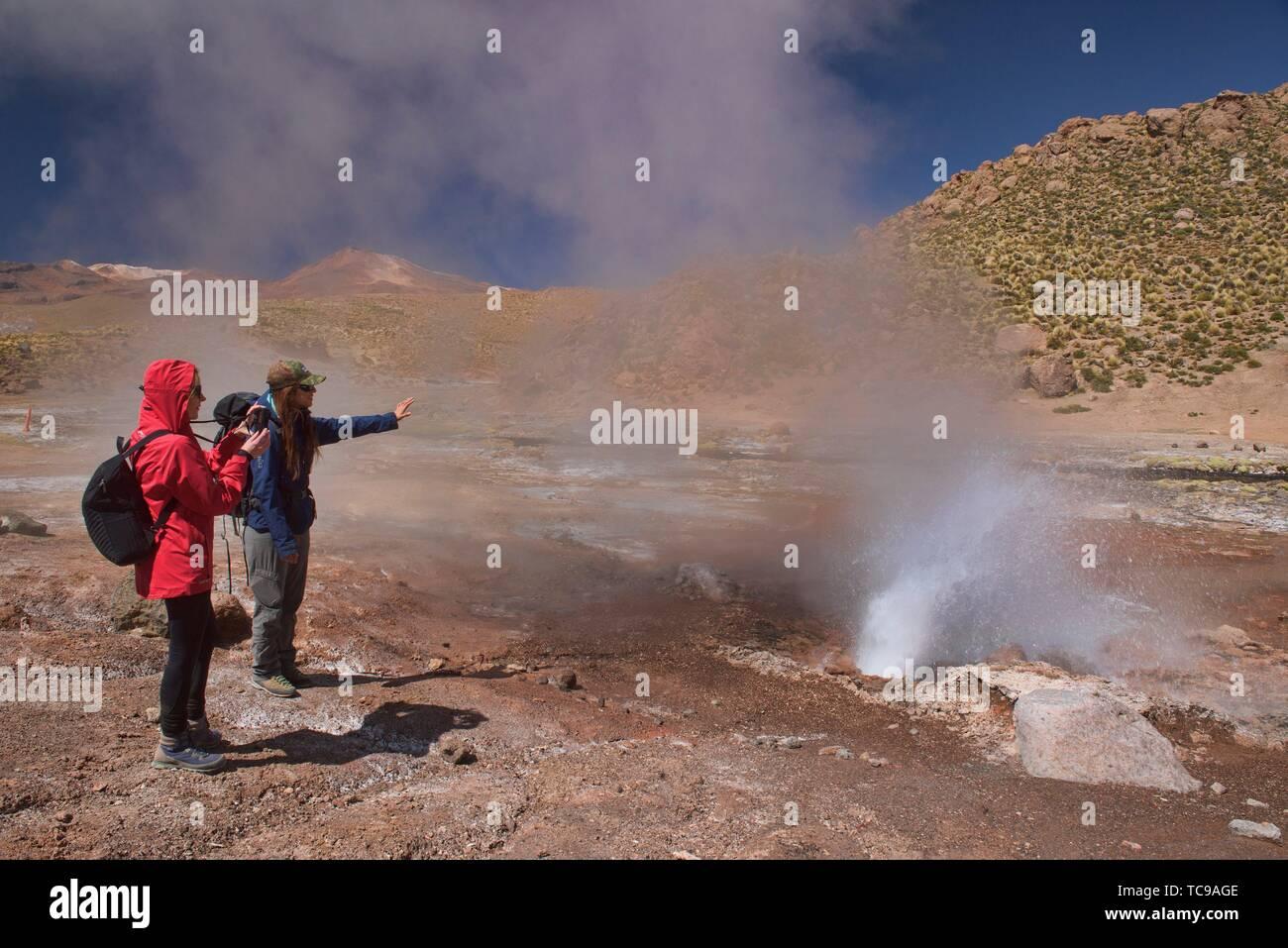 Watching a geyser erupt along the Rio Blanco, El Tatio, San Pedro de Atacama, Chile. Stock Photo