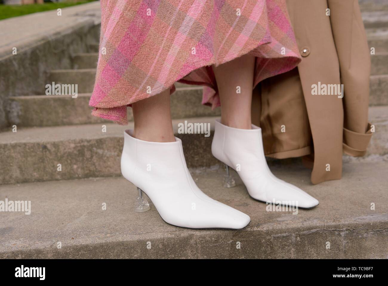 white high heels on stairs, stylish shoes of fashionable blogger woman during fashion week, in city Paris, France, in city Paris, France - Stock Image