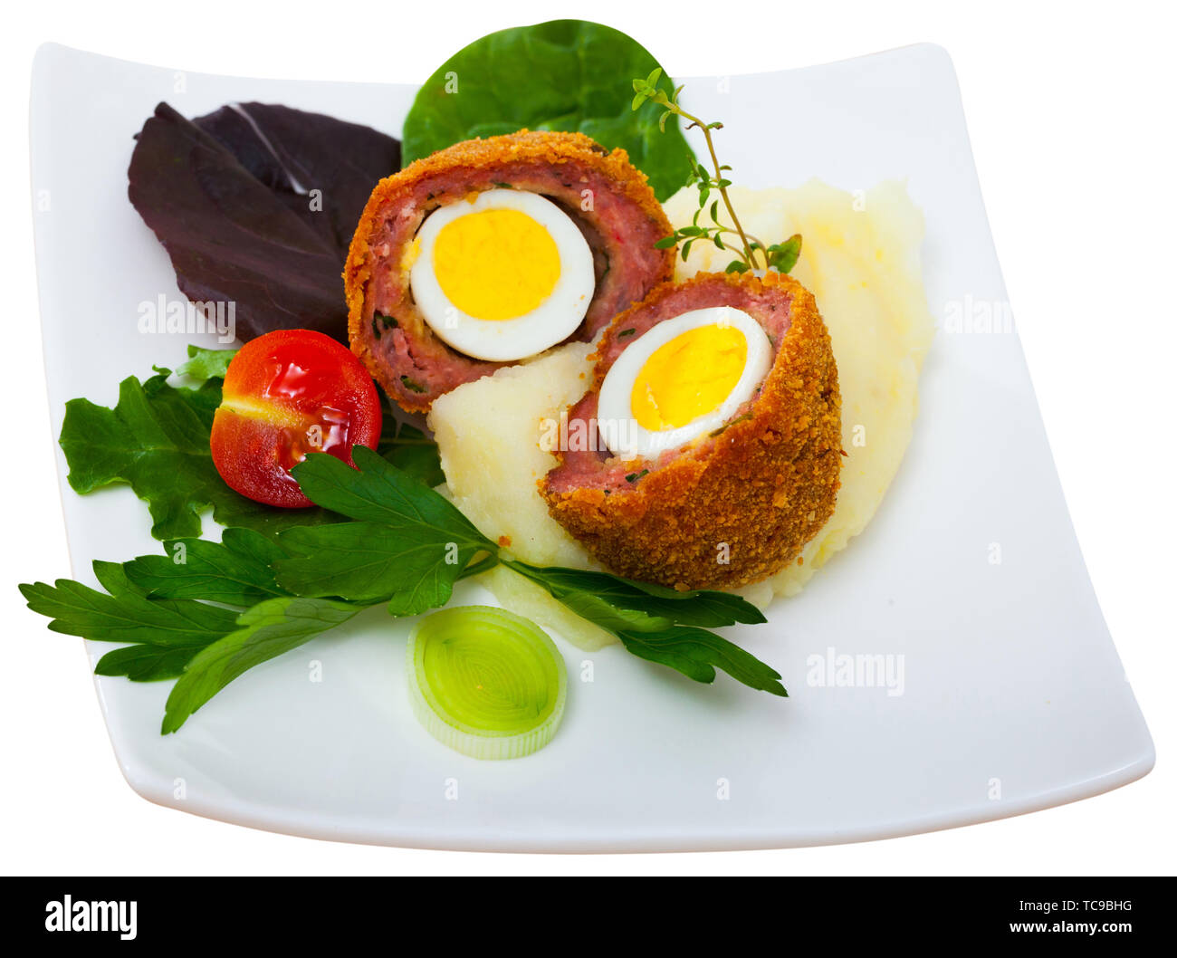 Hard-boiled quail egg wrapped in sausage meat, breaded and fried (Scotch egg) served with pureed potatoes, baked carrots, cherry tomatoes and greens. - Stock Image