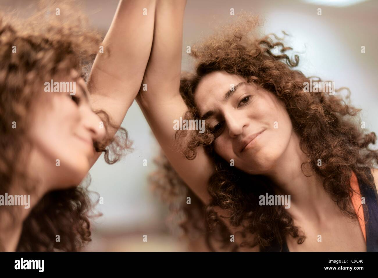 sporty woman leaning against mirror, mirror image, relaxed Stock Photo