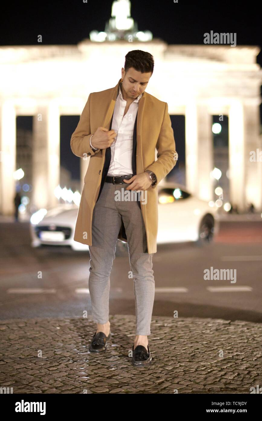young Afghan man looking down, in front of Brandenburg gate, at street at night, in Berlin, Germany. Stock Photo