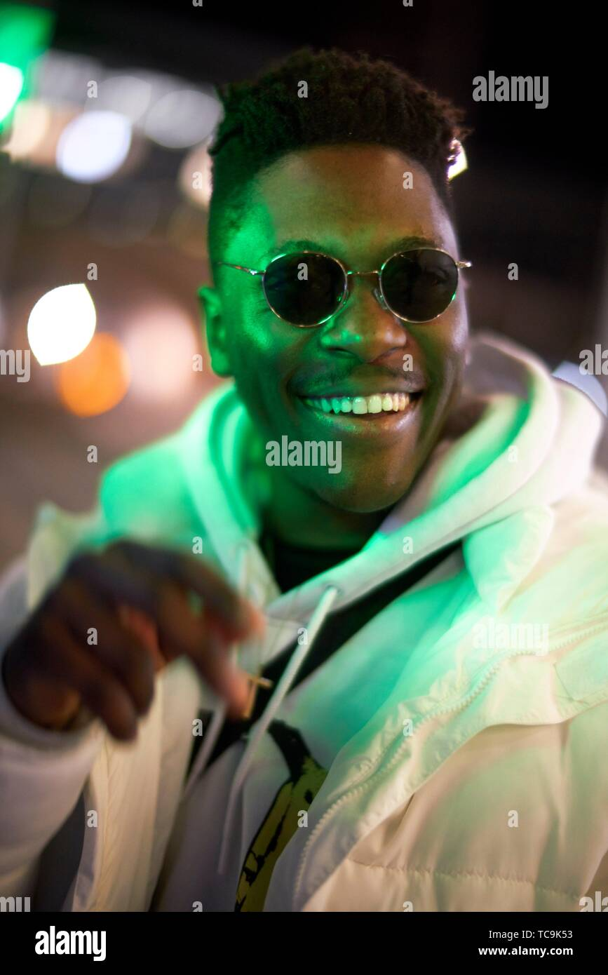 young happy laughing African man in green lights at night, wearing sunglasses, in Munich, Germany Stock Photo
