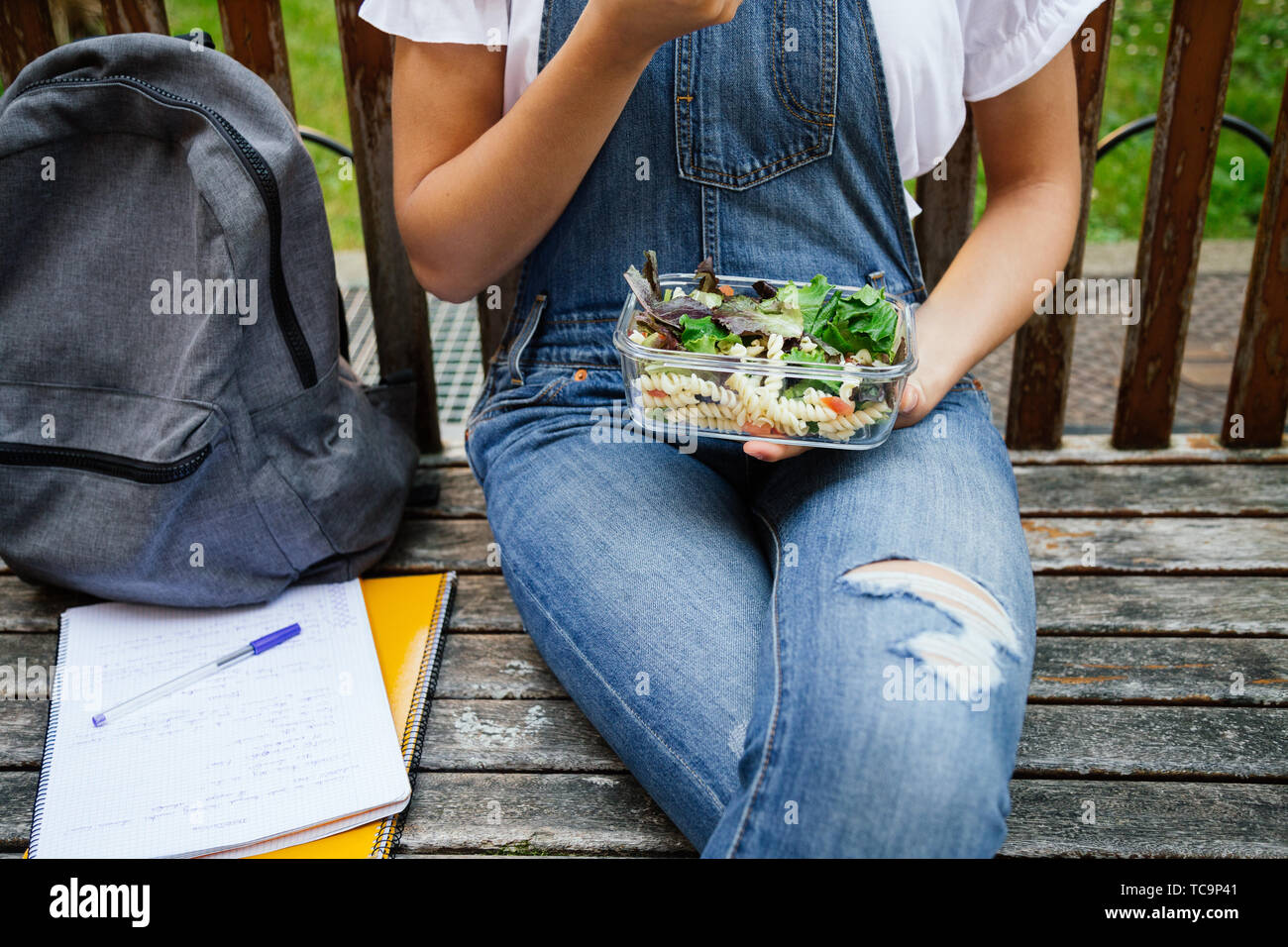 Midsection portrait of a student girl sitting in a bench while eating healthy salad with pasta in a glass lunch box Stock Photo
