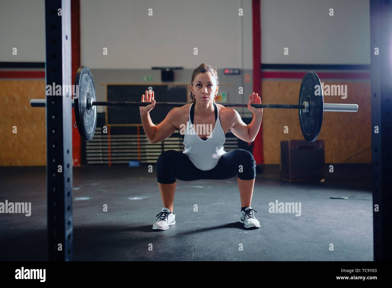 Athletic brunette young woman doing some weightlifting exercises. - Stock Image