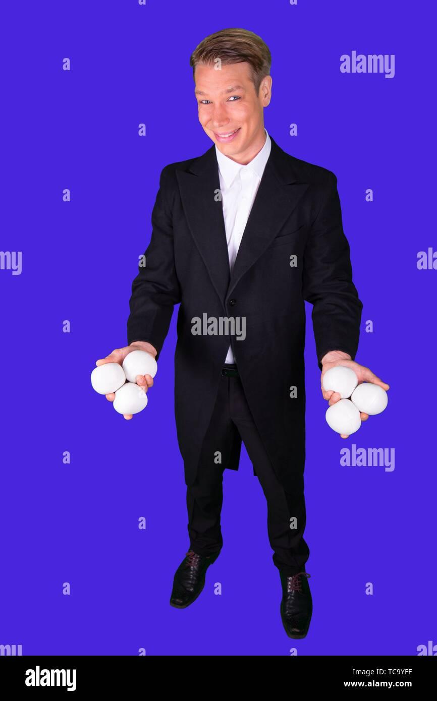 Juggler smiling with white juggling balls. - Stock Image