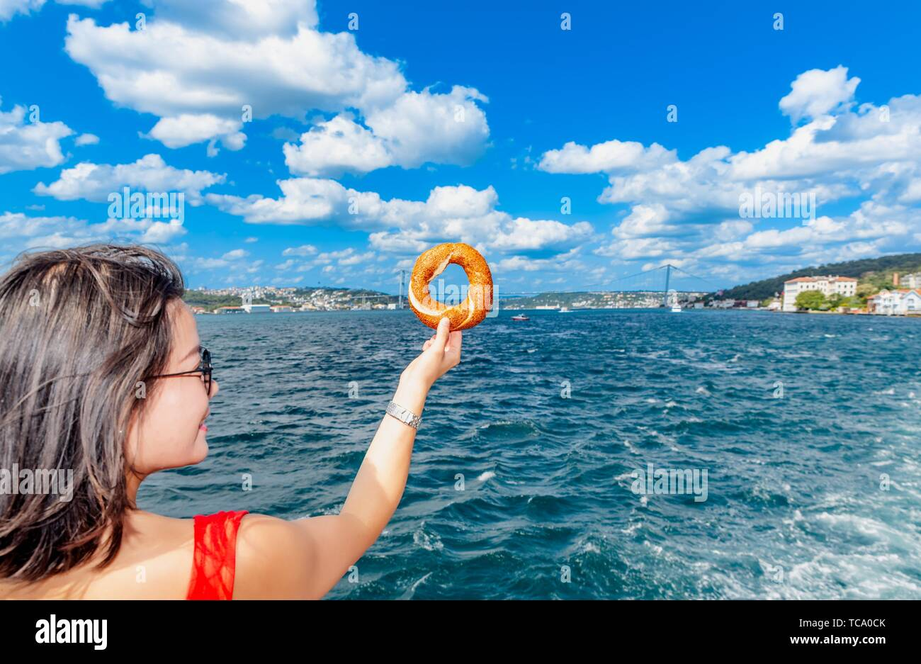 Beautiful Chinese woman holds traditional Turkish simit (bagel) with view of Bosphorus in Istanbul,Turkey. Stock Photo
