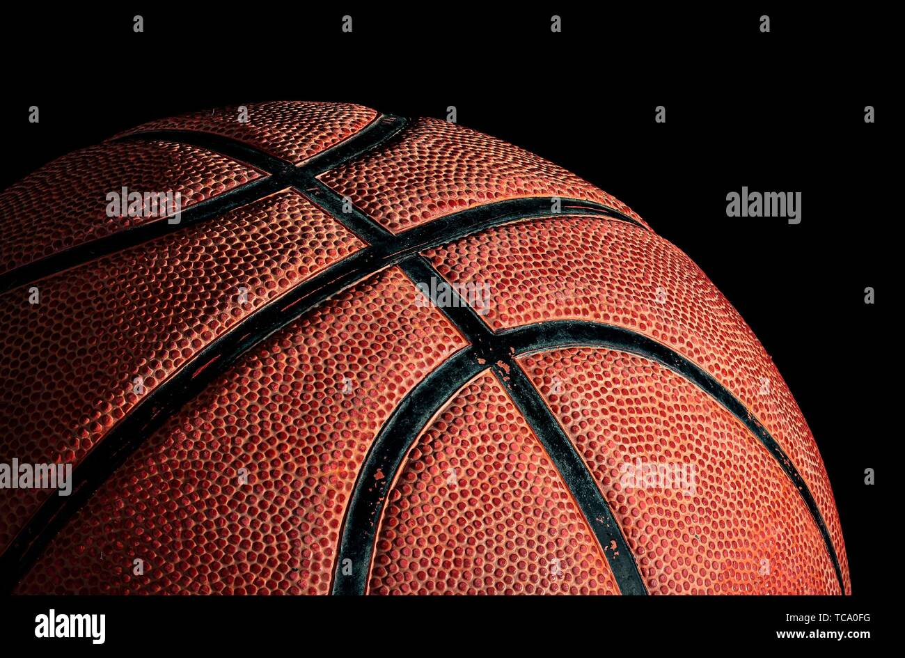 Part of basketball ball illuminated from above. On a black background. Side view. Stock Photo