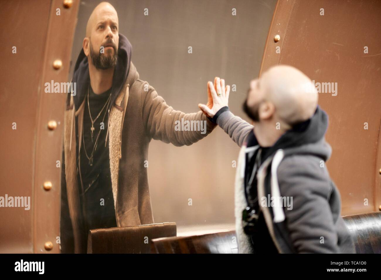 man looking at his distorted self in mirror in Paris, France - Stock Image
