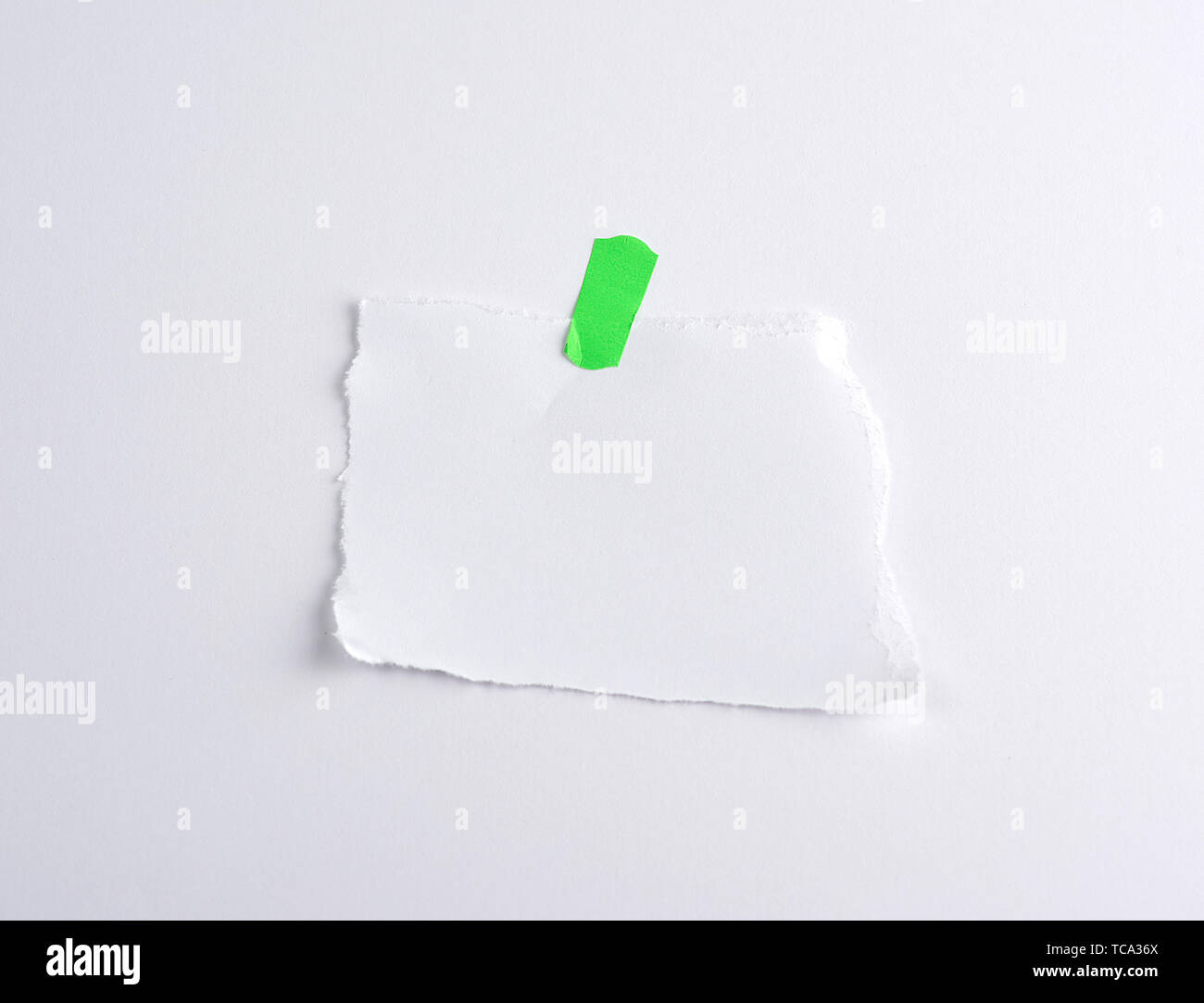 torn off white piece of paper glued to green velcro, white background - Stock Image