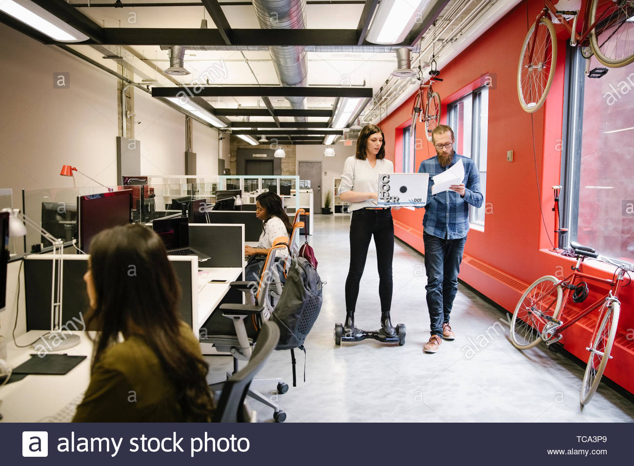 Businesswoman with laptop riding hover board in open plan office - Stock Image