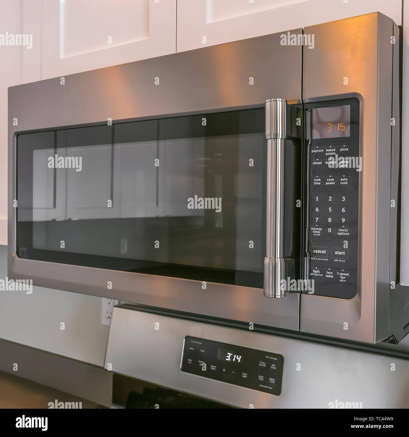 Square Close up of a microwave and white cabinets mounted on the wall of a kitchen Stock Photo