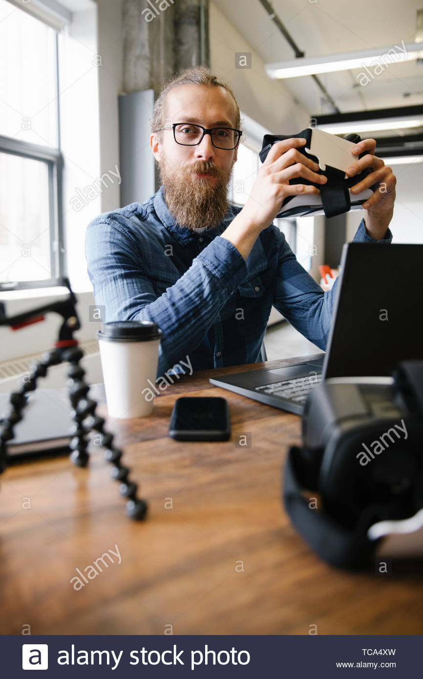 Portrait confident computer programmer with virtual reality simulator glasses in office - Stock Image
