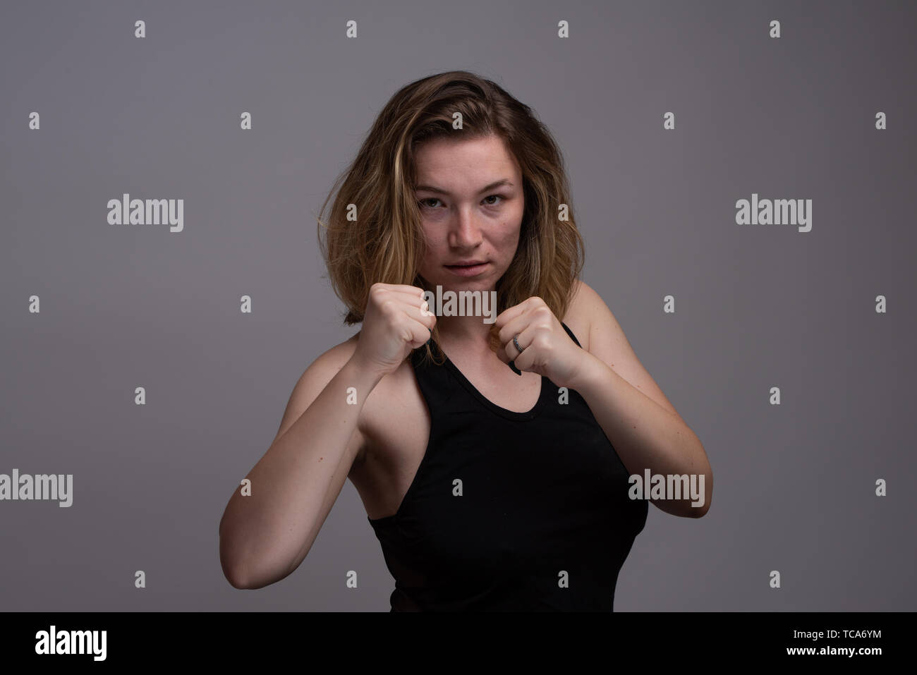 Blonde woman holding fists in aerobic punching class. Isolated subject against gray background. Shot in studio - Stock Image