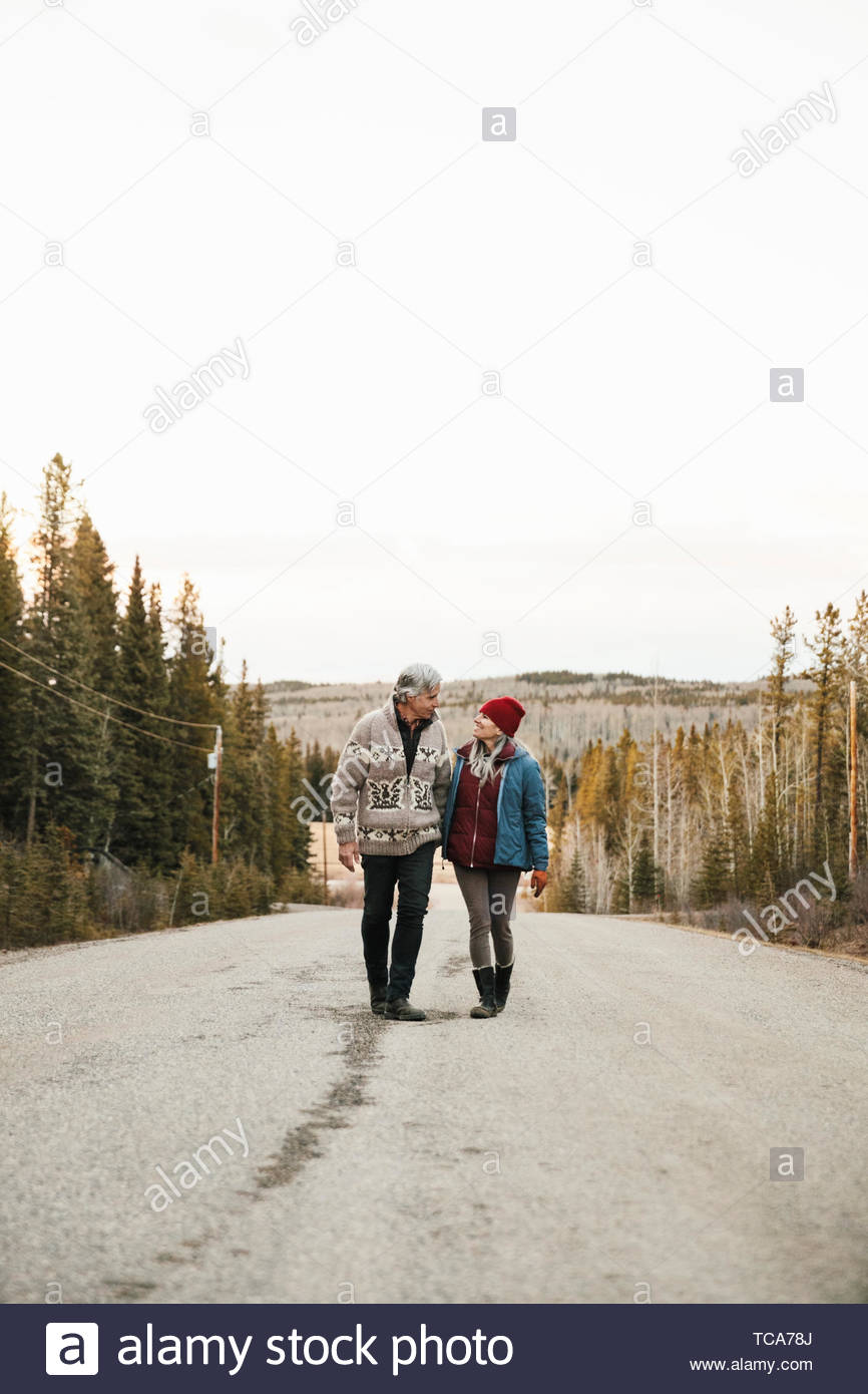 Affectionate couple walking on remote road - Stock Image